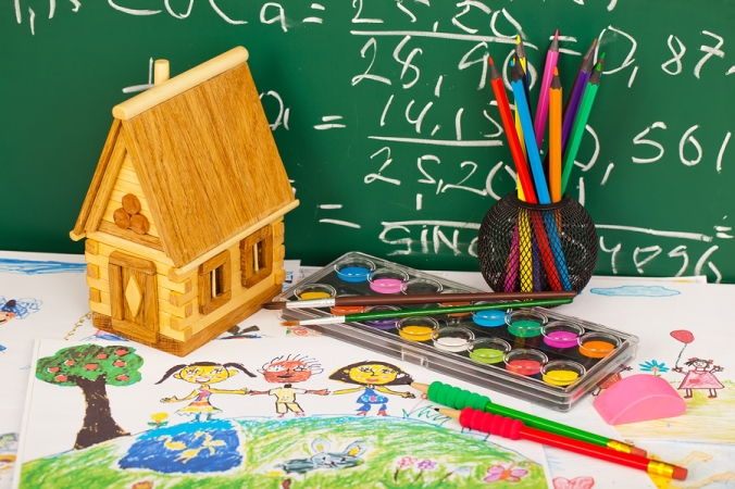 School supplies for teaching primary school students on a table in front of a chalkboard