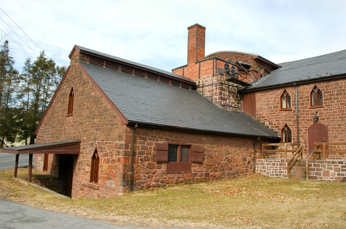 A view of Cornwall Iron Furnace, a National Historic Landmark, an old stone building with a sloped roof