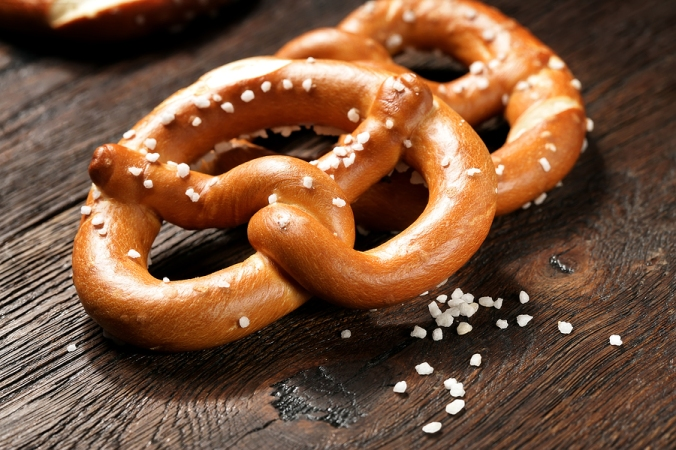Fresh pretzels with sea salt close-up on  dark board background