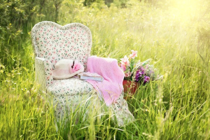 old fashioned padded chair in a field of grass,. Books, flowered hat and shawl draped on chair, wildflowers beside chair