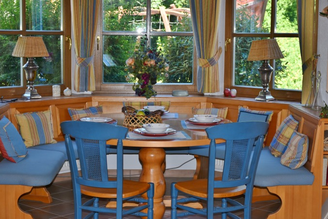 cozy circular breakfast nook with cushioned seats and chairs, table set with plates and bowls