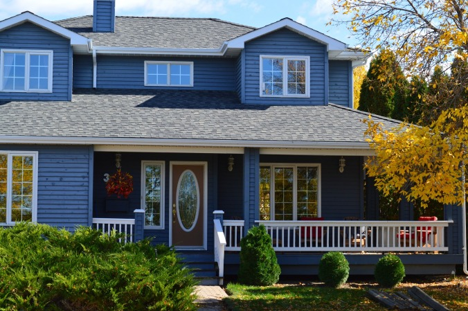 beautiful house with blue siding, covered porch and elegant front door with large oval window