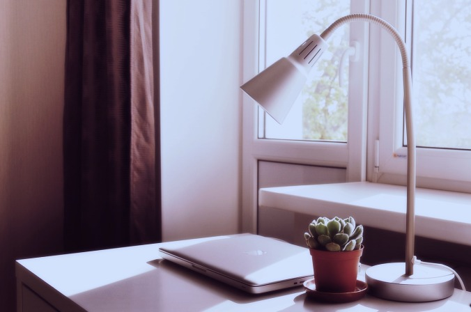 contemporary desk with macbook, desk lamp and small cactus plant, window in background