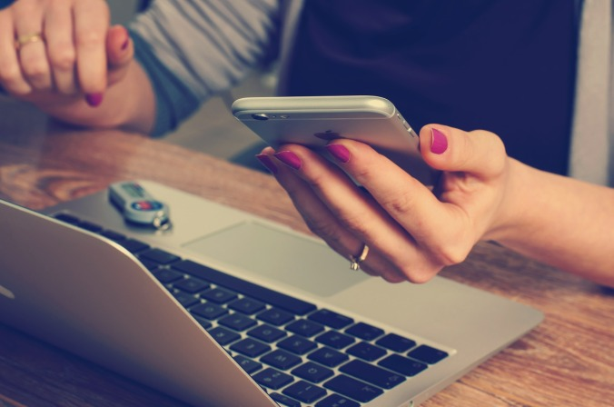 Close up of woman's hand holding iPhone, with a laptop on table in front
