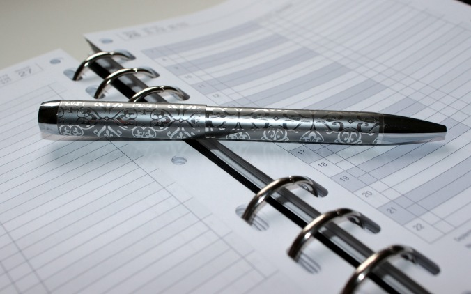 Silver pen lying on open calendar/date book