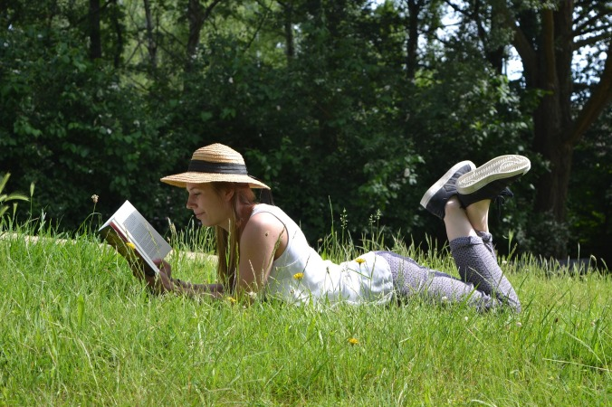 woman lying in grass on stomach, wearing straw hat and reading a book
