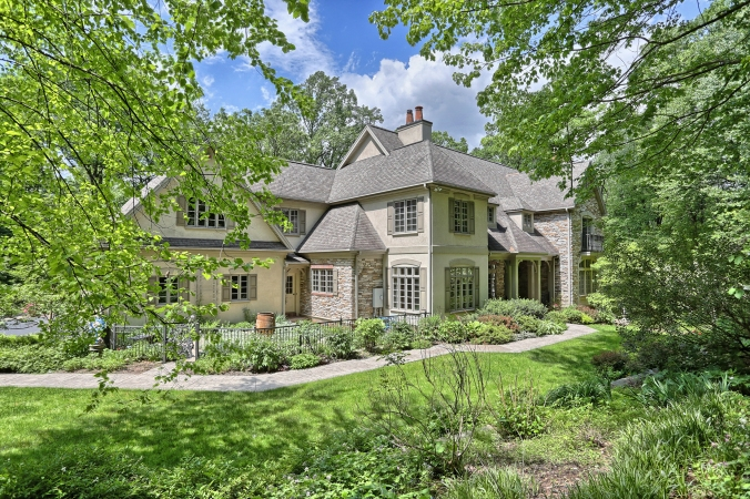 Distinguished home with asymmetrical roof peaks and large windows with shutters is tucked among trees for privacy. Setting features curving walk to front door and stately covered entrance
